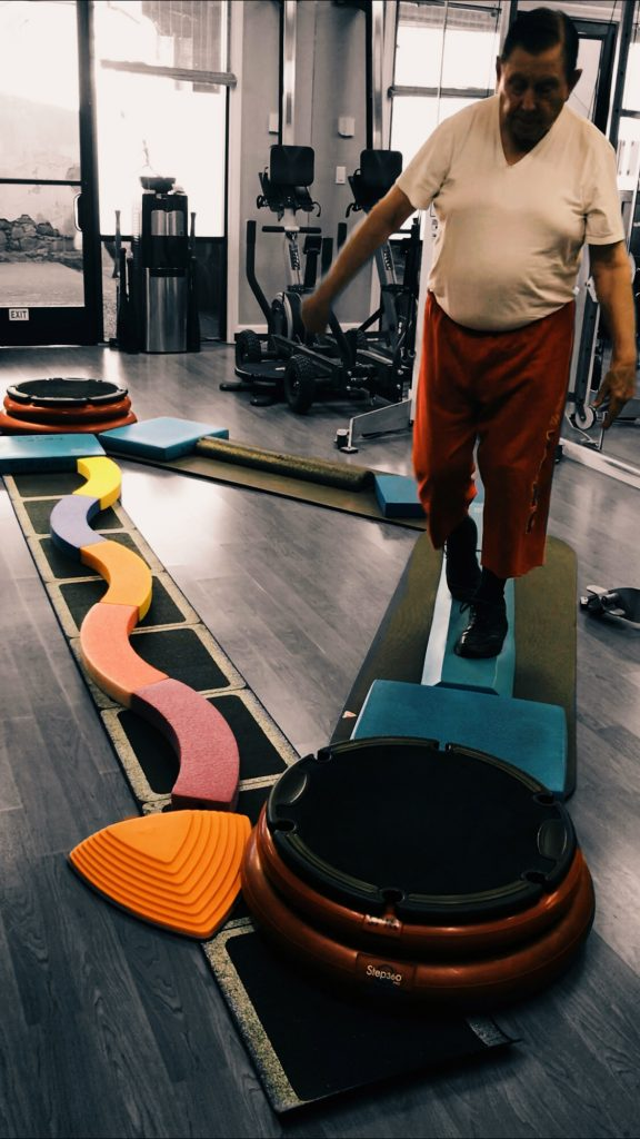 Man in gym navigating a fall-prevention obstacle course.