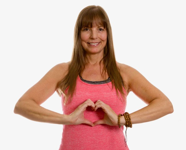 Woman at Body Balance Pleasanton forming a heary shape with her hands to indicated her interest in heart health.