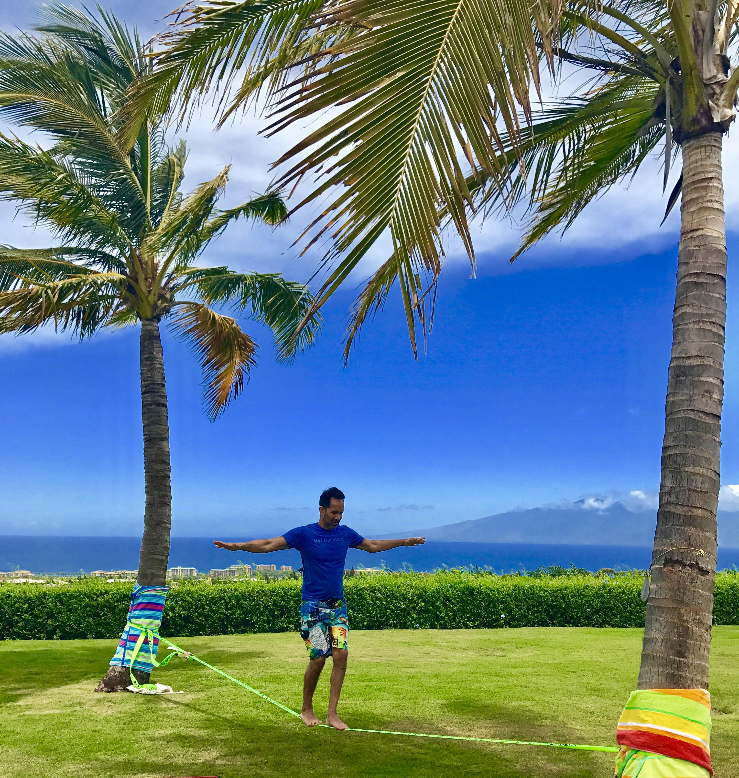 Man on slackline, part of his personal trainer to go program, in tropical setting.
