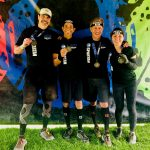 three group fitness friends and their personal trainer after a Spartan race