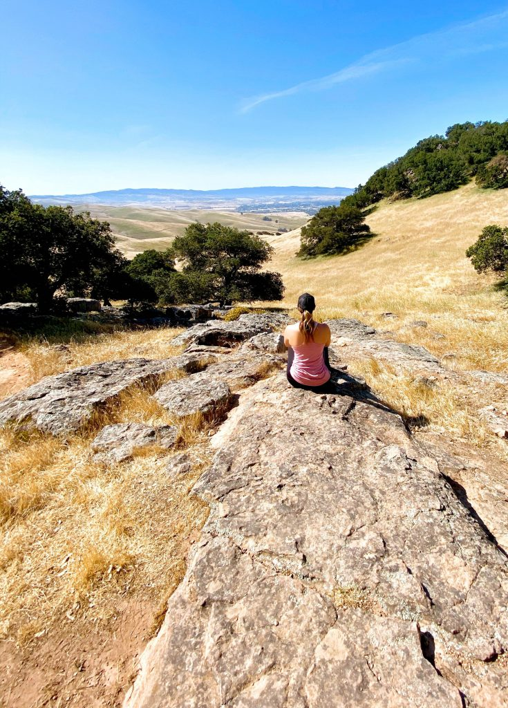 Massage therapist woman sitting on a rock looking at a view.