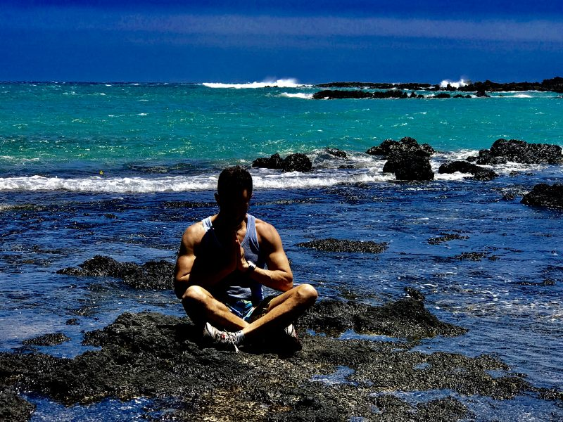 personal trainer sitting at the ocean meditating