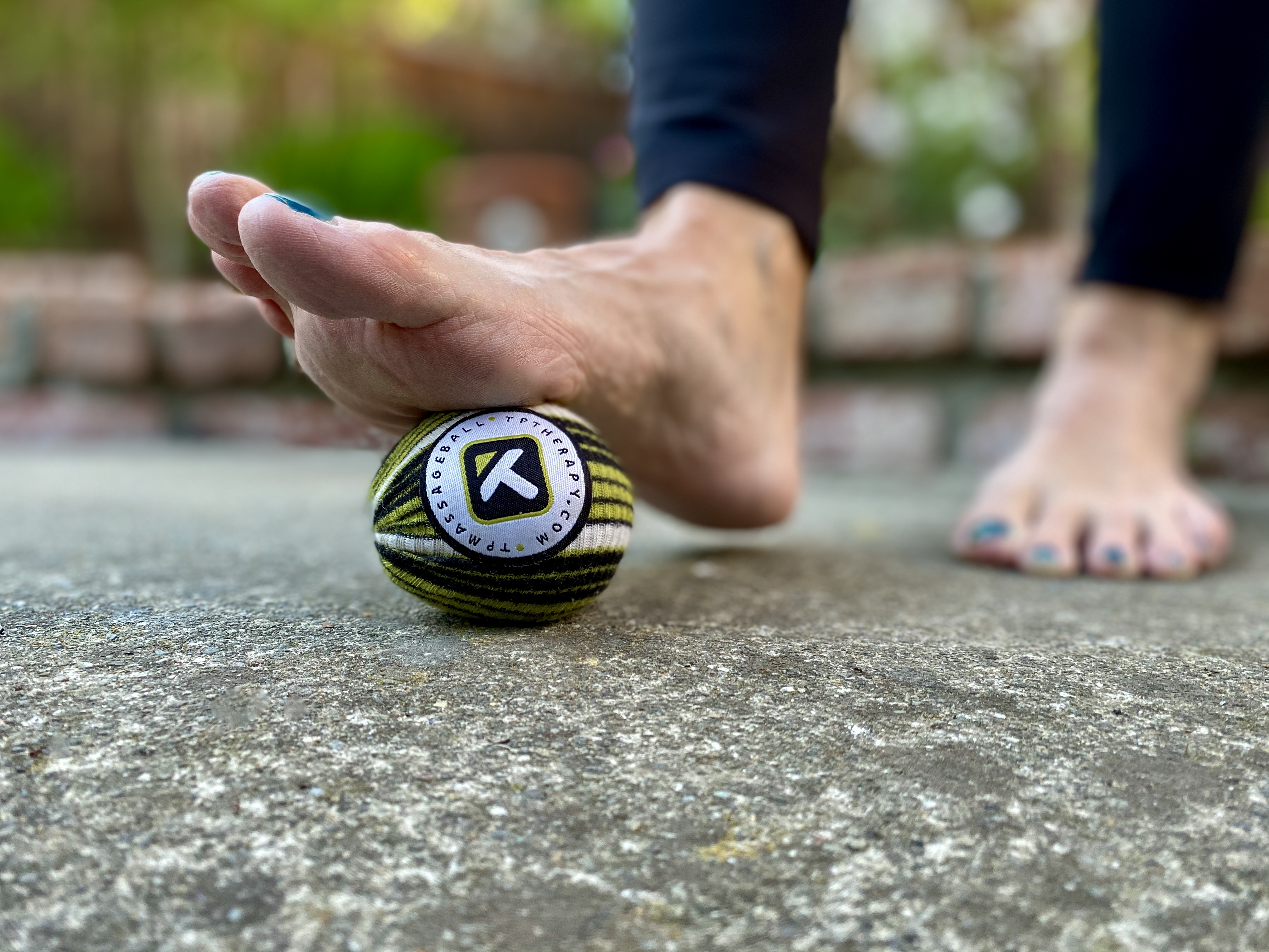 massage therapist's foot on a therapy ball